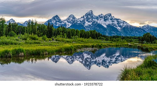 Snow mountains and green forest grassland reflect in the lake
