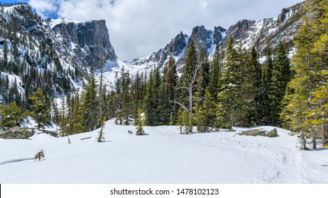 Snow Mountains - A panoramic Spring view of Hallett Peak and Flattop Mountain, surrounded by white snow and green forest, in Rocky Mountain National Park, Colorado, USA.