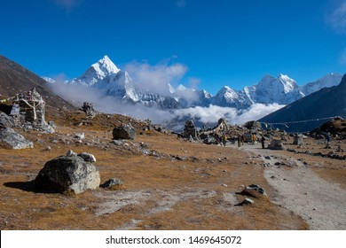 Snow mountains and sandy rocky path under a clear cloudy blue sky during the hike from Lobuche to Gorak Shep, Everest base camp trekking trail, EBC, Sagarmatha National Park, Nepal