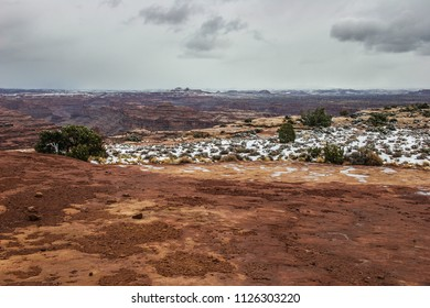 Snow the night before, has started to melt at White Crack camping area off the White Rim Road in the Island of the Sky District of Canyonlands National Park in Utah. Land formations in background.