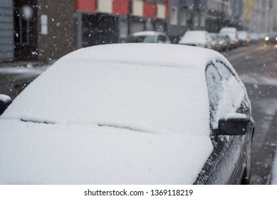 Snow on Car. White Snowflakes falling on parked dark car in winter on street in Germany.
