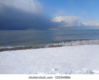 Snow on the coast and storm clouds over the sea