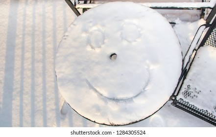 Snow on deck table with a face drawn on it, winter photography concept