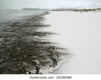 Snow on a deserted beach up to the water's edge