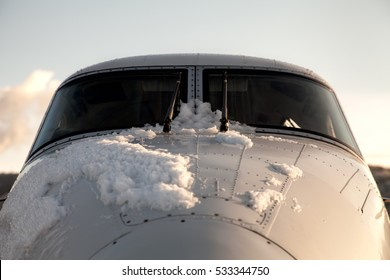 Snow on the front of the cockpit on an airplane