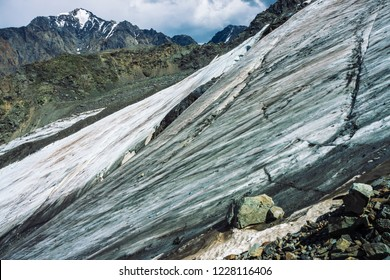Snow on giant mountain ridge. Wonderful ice terrain on mountainside. Icy steep slope. Amazing snowy rock. Climb high in mountains. Atmospheric minimalist landscape of majestic nature of highlands.