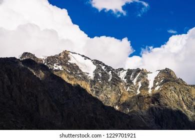 Snow on giant rocky ridge under blue cloudy sky. Dark steep mountainside. Amazing snowy mountain range in sunlight. Wonderful rocks. Atmospheric sunny landscape of majestic nature of highlands.