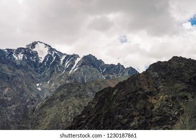 Snow on giant rocky ridge under cloudy sky. Atmospheric dark mountainside. Amazing snowy mountain range in overcast weather. Wonderful rocks. Wonderful shaded landscape of majestic nature of highlands