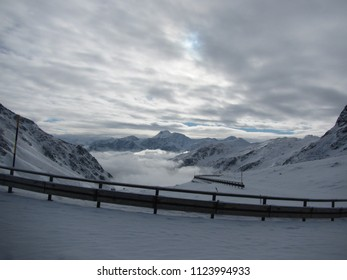 Snow on Great St Bernard Pass road and impossibility to move forward - railing standing out. Instead it is used a sky climbing ground. Lake and valley in the back and shrouded cloudy sky above