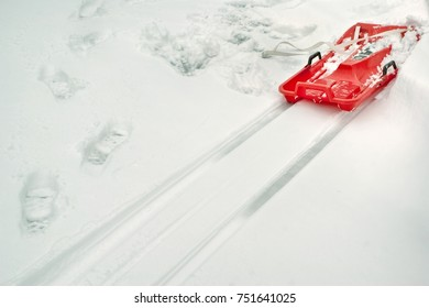 Snow on the ground, foot steps and tracks of red sleigh. Winter play and activity concept.