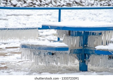 snow on icicles on bright blue park bench and table in Holland Michigan