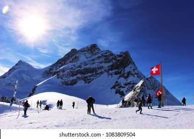 Snow on mountains and Swiss flag with mountain background.  Snowy summit with deep blue sky on a sunny day in Jungfrau region, Switzerland.