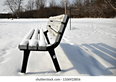 Snow on a park bench with shadow