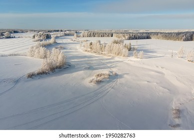 The snow on the river ice is decorated with snow mobile tracks. The frozen river is an excellent track for high speed snow mobile racing.