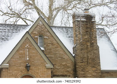 Snow on roof with chimney of yellow brick historic home with birch tree in the background