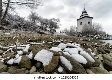 Snow  on stones at pebble beach on reservoir Liptovska Mara, Slovakia, White tower of church at background