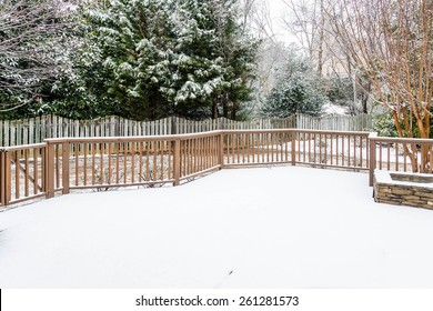 Snow on wood deck and fence with evergreens in background