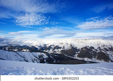 Snow peaks of mountains with blue sky and beautiful clouds. Winter tourism in Russia, Arkhyz. Snow valley on horisontal landscape.