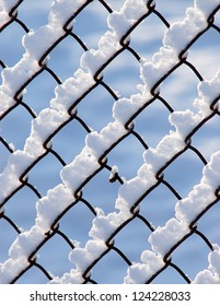 Snow piled on the wires of a chain link fence