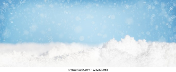 Snow piles on ground and falling in blue sky. Horizontal web banner or social media cover with room for text.
