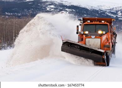 Camino de desalojo de camiones de arado de nieve después de la tormenta de nieve blanca para el acceso de vehículos