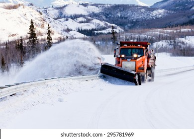 Snow plough truck clearing road after whiteout winter snowstorm blizzard for vehicle access