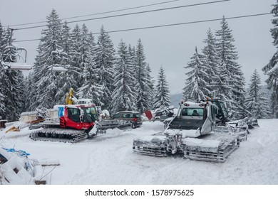 Snow ploughs with caterpillar tracks are parked up in a European ski resort having been out clearing snow in the resort.Ski lift chairs and pine forest in this winter scene.Image