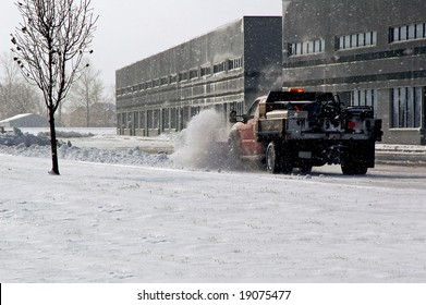 Snow plow cleaning up the parking lot.