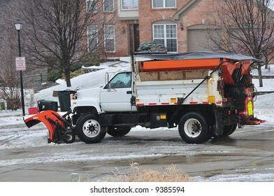 A snow plow cleaning the road in a suburban neighborhood in Kentucky, USA.