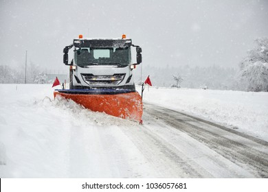 Snow plow clearing a snowy road