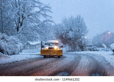 A snow plow with headlights on driving through a snowy landscape on a winter's night