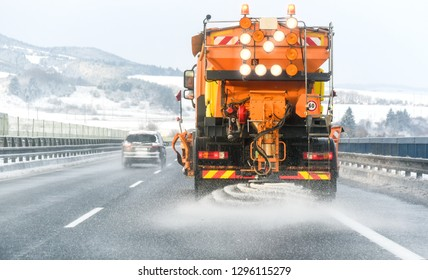 Snow plow on highway salting road. Orange truck deicing street. Maintenance winter gritter vehicle.