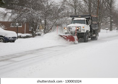 Snow plow removing snow from street.