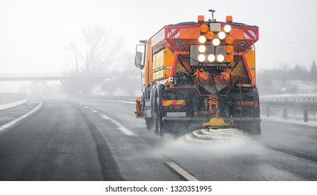 Snow plow salting street in winter time. Orange truck deicing. Maintenance winter vehicle back side.  Focus on front.