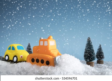 Snow plow. Toy car in a little winter landscape. Concept of road cleaning and road safety.