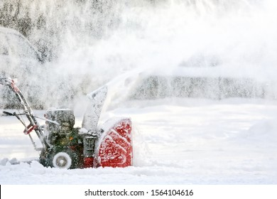 snow plow tractor at winter removing white snow out of road against heavy snowfall weather background. Closeup side view of snow plowing process on city street in cold season environment