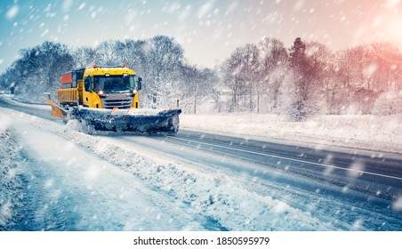 Snow plow truck cleaning snowy road in snowstorm. Snowfall on the driveway.