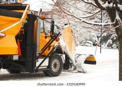Snow plow truck clearing road after winter snowstorm blizzard, Ontario, Canada