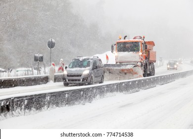 Snow plow truck on the highway during a blizzard in winter