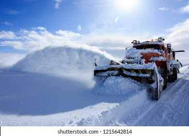 Snow plowing truck, huge heavy machine service car, snow flakes and splash off road, winter cold snowy season, snow cleaning ratrack truck, sunny blue sky day at cold Russian arctic north, industrial