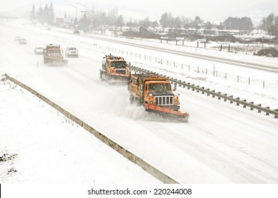 Snow plows clearing the freeway on Interstate 5 during a winter snow and freezing rain storm