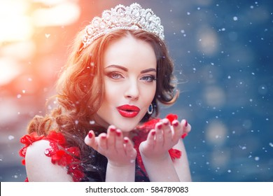 Snow Queen in red. Winter woman in crown in a red dress and red lipstick. Girl with snowflakes
