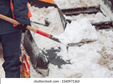 Snow removal in the city. Worker helps shovel snowplow.