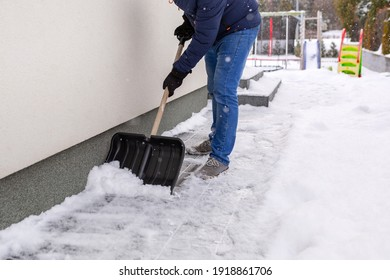 Snow removal of the driveway in front of the house with a shovel