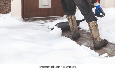 Snow removal. Man in rubber boots clears snow from the yard wide plastic shovel