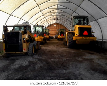 Snow removal plows and tractors sitting in a warehouse - ready for winter