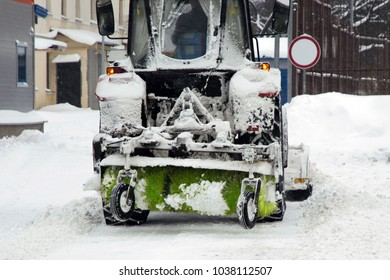 snow removal, urban. Tractor snowplow with a rotary brush removes snow from city streets after the storm