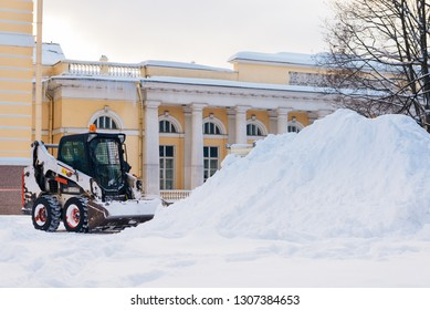 Snow removal vehicle removing snow. Tractor clears the way after heavy snowfall in St. Petersburg, Russia winter