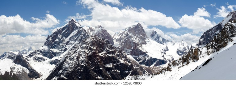 Snow and rocks in central asia, with clounds and blue sky