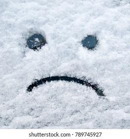 Snow sad face on the car window